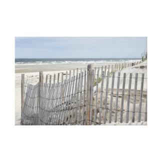 Weathered beach fence and ocean beach canvas print