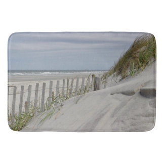 Weathered fence and sand dunes at the beach bath mat