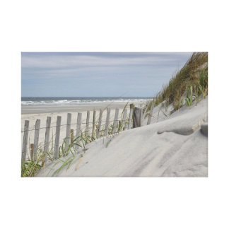 Weathered fence and sand dunes at the beach canvas print