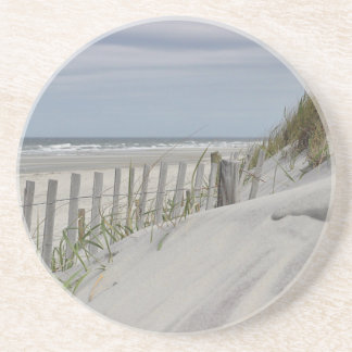 Weathered fence and sand dunes at the beach coaster