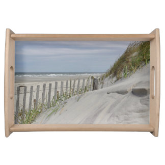 Weathered fence and sand dunes at the beach serving tray