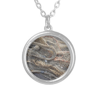 Weathered fishing nets on a harbor pier silver plated necklace