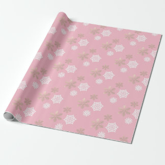 white and gold snowflakes against pale pink wrapping paper