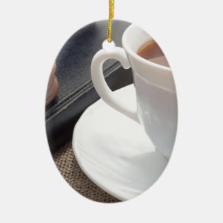 White cup of hot cocoa and a chocolate biscuit ceramic oval ornament