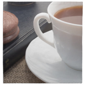 White cup of hot cocoa and a chocolate biscuit napkin