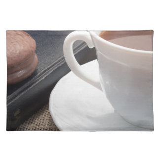 White cup of hot cocoa and a chocolate biscuit placemat