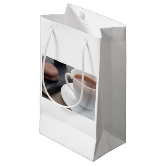 White cup of hot cocoa and a chocolate biscuit small gift bag