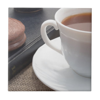 White cup of hot cocoa and a chocolate biscuit tile