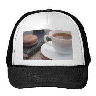 White cup of hot cocoa and a chocolate biscuit trucker hat