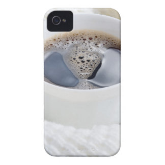White cup of hot coffee surrounded by a white wool iPhone 4 cover