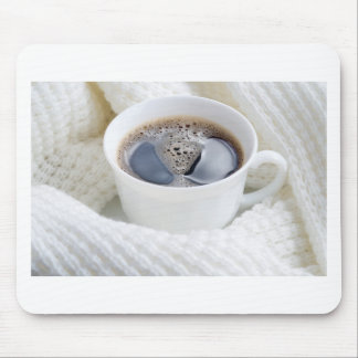White cup of hot coffee surrounded by a white wool mouse pad