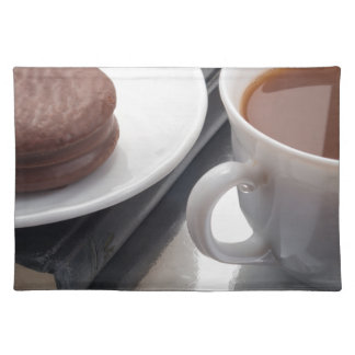 White cup with cocoa and chocolate covered biscuit place mats
