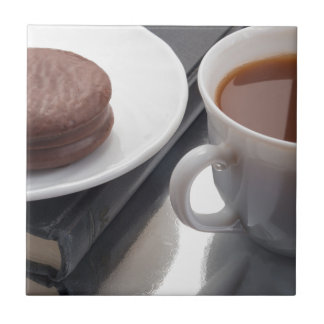 White cup with cocoa and chocolate covered biscuit tile