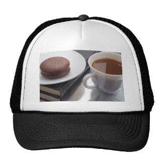 White cup with cocoa and chocolate covered biscuit trucker hat