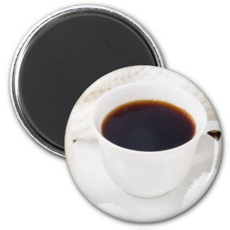 White cup with hot coffee and woolen mittens magnet