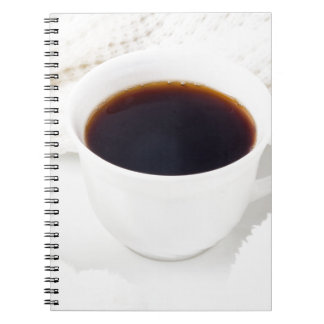 White cup with hot coffee and woolen mittens notebooks