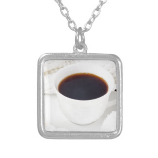 White cup with hot coffee and woolen mittens silver plated necklace