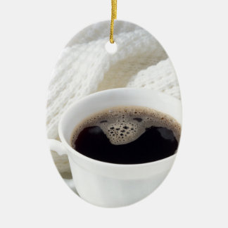 White cup with hot coffee wrapped in a white woole ceramic ornament