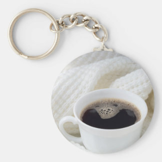 White cup with hot coffee wrapped in a white woole keychain