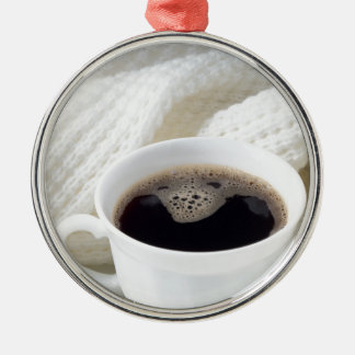 White cup with hot coffee wrapped in a white woole metal ornament