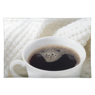White cup with hot coffee wrapped in a white woole placemat
