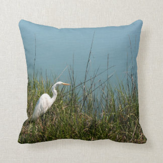 White egret standing in grass w water throw pillow