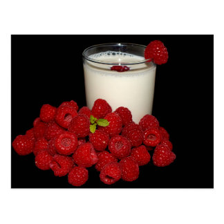 white milk with red raspberries on a black postcard