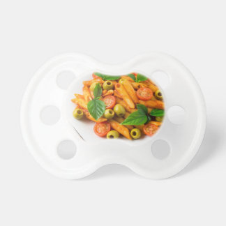 White plate of penne pasta decorated with cherry baby pacifiers
