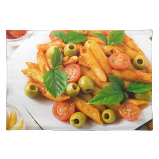 White plate of penne pasta decorated with cherry placemat