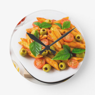 White plate of penne pasta decorated with cherry round clock
