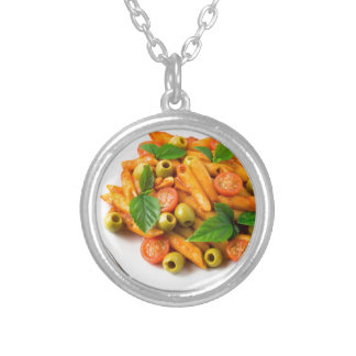 White plate of penne pasta decorated with cherry silver plated necklace