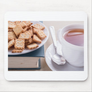 White plate with cookies on old book mouse pad