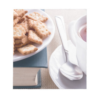 White plate with cookies on old book notepad