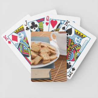 White plate with cookies on the old book bicycle playing cards
