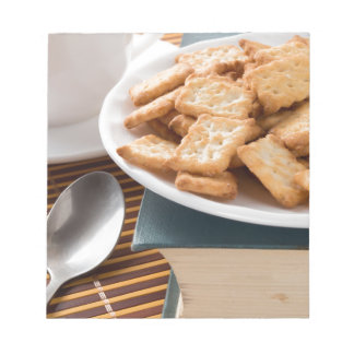 White plate with cookies on the old book notepad