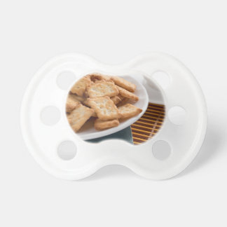 White plate with cookies on the old book pacifier