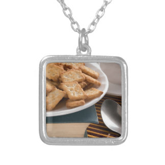 White plate with cookies on the old book silver plated necklace