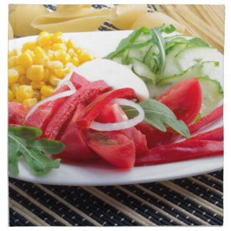 White plate with slices of fresh tomatoes napkin