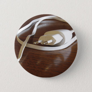 White smartphone charger on wooden table 2 inch round button