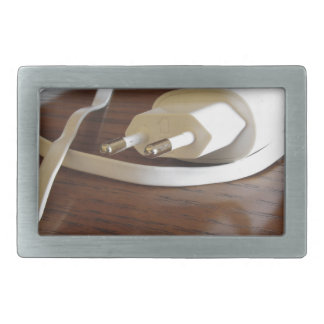 White smartphone charger on wooden table belt buckle