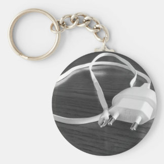 White smartphone charger on wooden table keychain