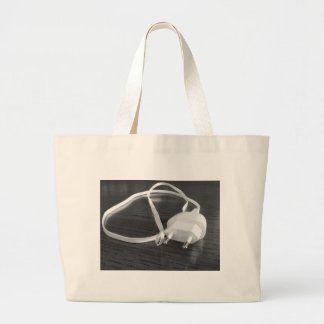 White smartphone charger on wooden table large tote bag