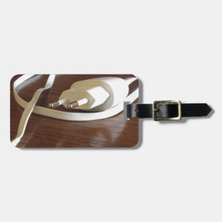 White smartphone charger on wooden table luggage tag