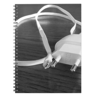 White smartphone charger on wooden table notebook