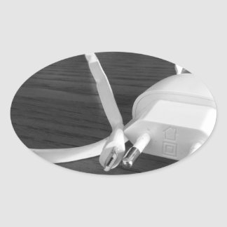 White smartphone charger on wooden table oval sticker