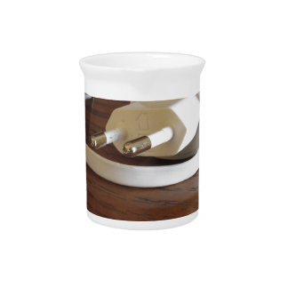 White smartphone charger on wooden table pitcher