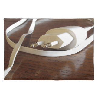 White smartphone charger on wooden table placemat