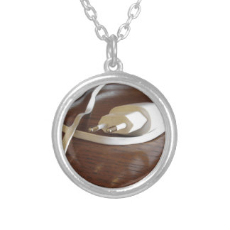 White smartphone charger on wooden table silver plated necklace