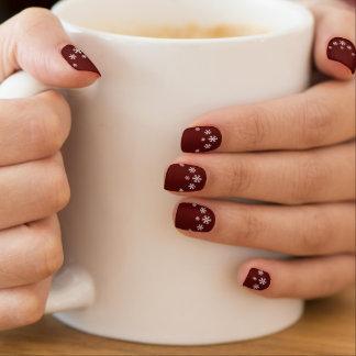 White snowflakes on burgundy minx nail art