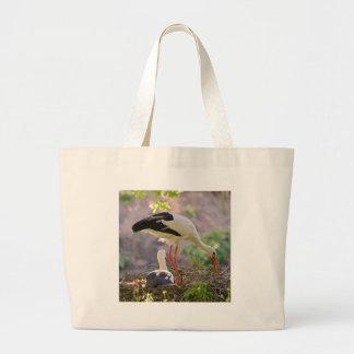 White storks on its nest large tote bag